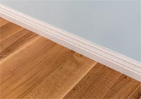 closeup white baseboard on white oak hardwood floor