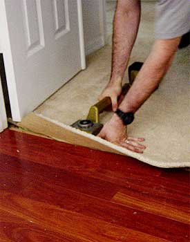 Nudge carpet to wood with knee kicker