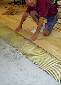 Laying hardwood into adhesive